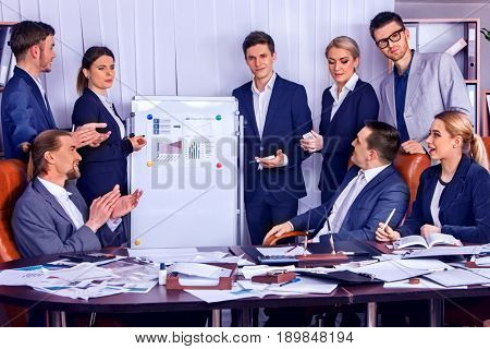 Business people office life of team people working with papers sitting table. Cabinets with folders and jalousie background. Schemas and diagrams on presentation and demonstration. Organizational