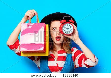 Woman With Alarm Clock And Shopping Bags