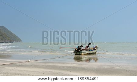Small woodenl fishing boat (Longtail boat) anchored on beach at low tide in Thailand