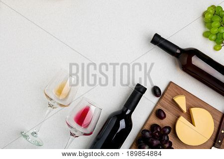 Two wine glasses with red and white wine, bottles of red wine and white wine, cheese on white background. Horizontal view from the top. Mock-up. Copy space. Flat lay