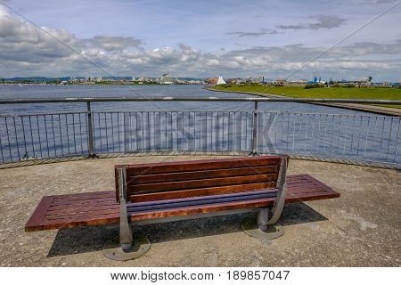 View of Cardiff Bay from the Barage with bench and railing in the foreground.
