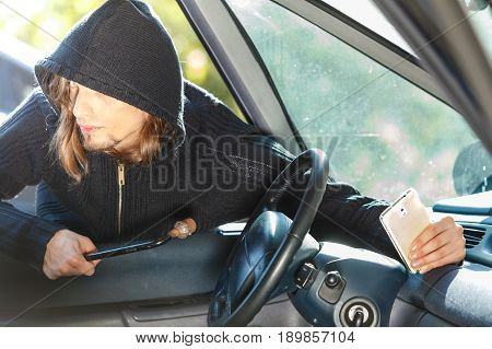 Anti theft system problem concept. Burglar thief man wearing black clothes breaking into car and stealing smartphone