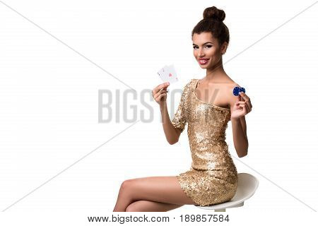 Beautiful young woman holding two ace of cards and two chips in her hand isolated on white. A woman is sitting on a white chair without a backrest. Studio shot. Poker