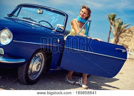 Beautiful woman sitting in retro cabriolet car on the beach