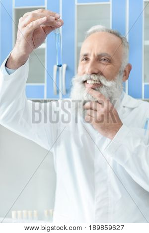 Smiling Senior Bearded Scientist In White Coat Holding Tube With Reagent In Chemical Laboratory