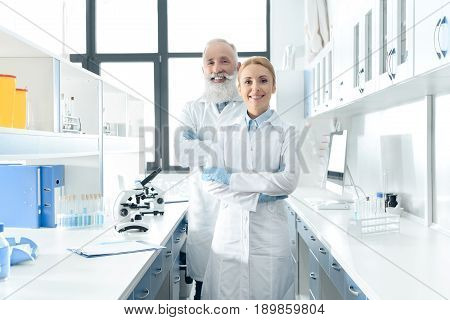 Two Happy Chemists In White Coats Standing In Chemical Laboratory With Microscopes And Flasks
