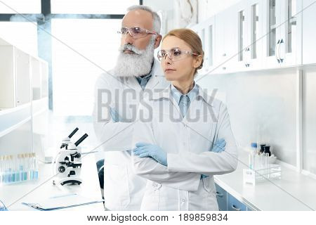 Two Confident Scientists In White Coats And Goggles Looking Away And Posing In Chemical Laboratory