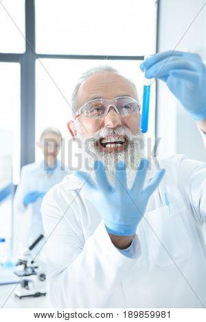 Excited Bearded Chemist Holding Test Tube With Reagent And Gesturing