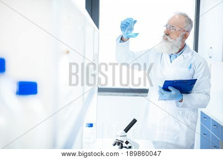 Senior Bearded Scientist Holding Flask With Reagent And Clipboard In Chemical Lab