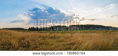 Panoramic rural landscape. Sunset in the countryside. A field of yellowed grass and an evening sky with picturesque clouds. Panorama shot.