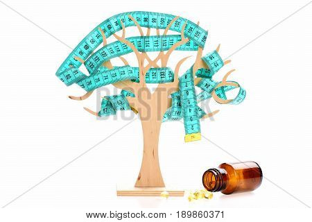 Capsules of cod liver from glass bottle next to decorative wooden tree with measuring tape on branches isolated on white background. Diet concept
