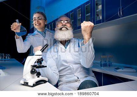 Scientist Using Microscope While Colleague Holding Reagent In Tube In Lab. Scientists Working Togeth