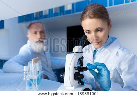 Focused Scientist Using Microscope While Working In Lab With Colleague Behind In Lab