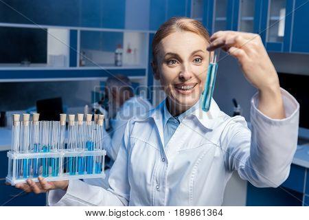 Happy Chemist In Lab Coat Holding Tubes At Laboratory
