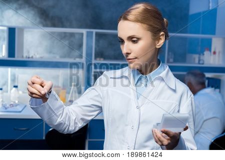 Pensive Chemist In Lab Coat Looking At Samples At Laboratory