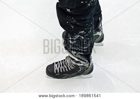 Closeup of male feet in black skates standing on ice