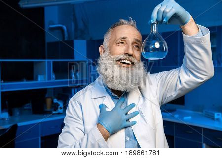 Happy Grey Haired Scientist In Lab Coat Holding Flask With Reagent