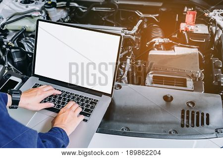 Professional Car Mechanic Working In Auto Repair Service Using Laptop On Car