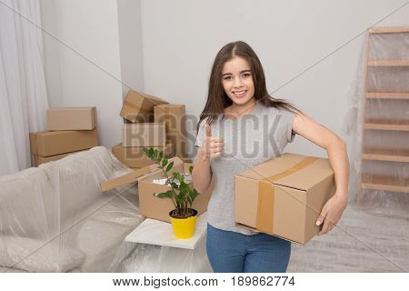Beautiful girl moving in the new apartment. Woman after relocating standing in the room holding cardboard box and showing her thumb up.