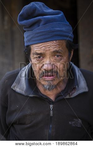 HIMALAYAS ANNAPURNA REGION NEPAL - OCTOBER 16 2016 : Portrait old man in traditional dress in Himalayan village Nepal