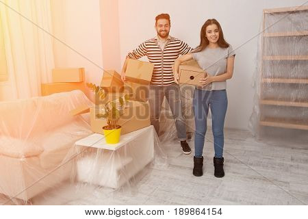 Toned image. Happy young couple unpacking or packing boxes and moving into a new home. Man and woman standing in new home holding unpacked boxes.