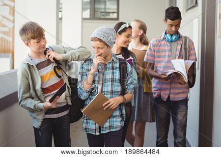 Group of classmate walking in corridor at school