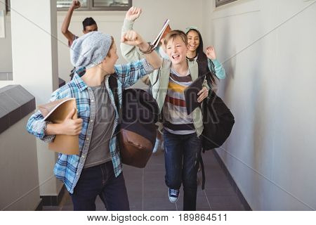Group of classmate running in corridor at school