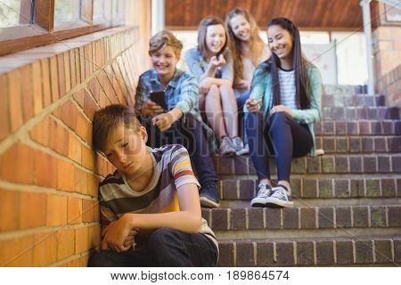 School friends bullying a sad boy in school corridor at school