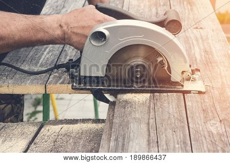 Male hand cuts with a circular saw a piece of Board on a Sunny day. Toned. A horizontal frame.
