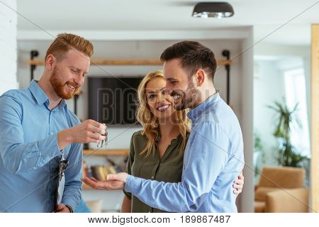 Shot of young satisfied couple became owners of the new house.