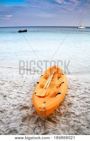 Holiday activities. Kayak on empty beach. kayak on the tropical beach and clear blue sky.