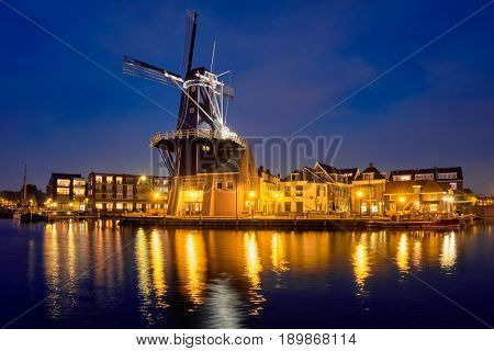 View of Harlem cityscape with landmark windmill De Adriaan on Spaarne river in the night illuminated. Harlem, Netherlands