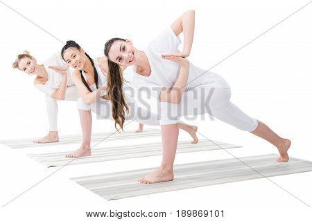 Smiling Young Women Practicing Variation Of Revolved Side Angle Pose (parivrtta Parsvakonasana)