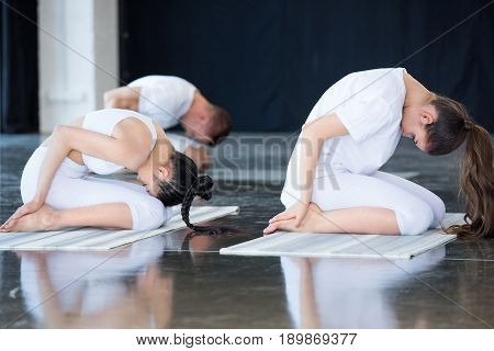 women doing yoga in child pose (Balasana) with instructor at exercise room