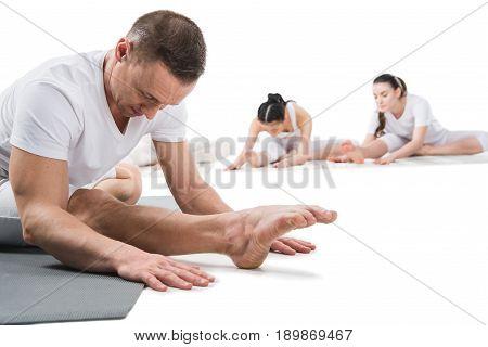 instructor doing head to knee pose (janu shirshasana) with women isolated on white