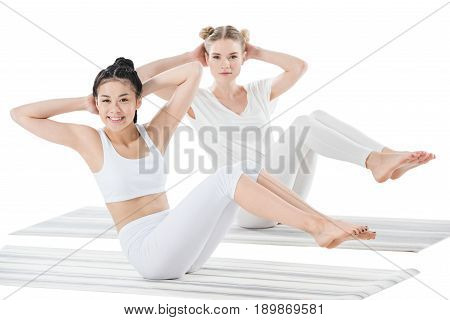 Multiethnic Girls Doing Side Abdominal Crunches And Looking At Camera Isolated On White