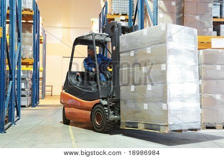 Forklift loader moving at warehouse with a cardboard boxes