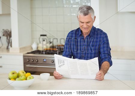 Senor man reading newspaper in kitchen at home