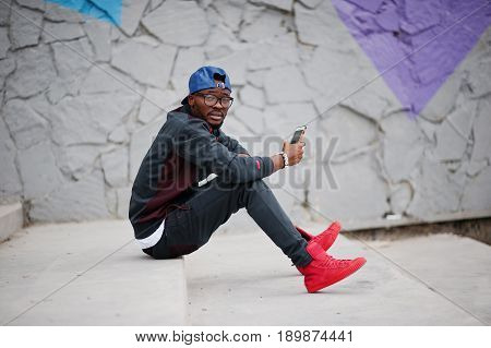 Portrait Of Stylish African American Man On Sportswear, Cap And Glasses Sitting On Stairs With Phone