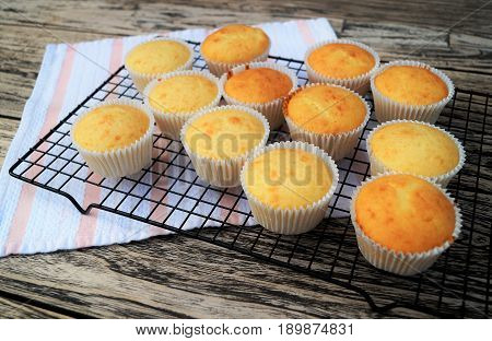 Baking Cupcakes in Progress. An authentic kitchen scene of baking at home with freshly baked cupcakes on a cooling rack