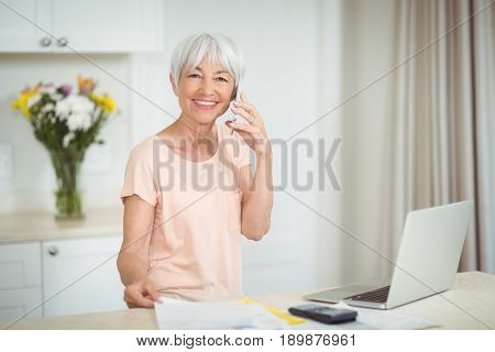 Portrait of senior woman talking on mobile phone in kitchen at home