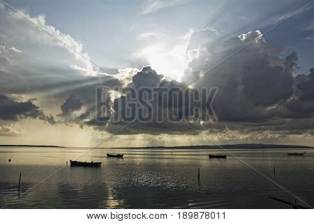 After the thunderstorm sunset on the lagoon. In the background fishing boats. Mediterranean Sardinia islands.