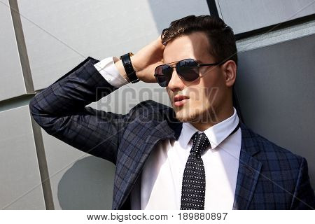 fashionable young man dressed in the gray background beautiful urban architectural form
