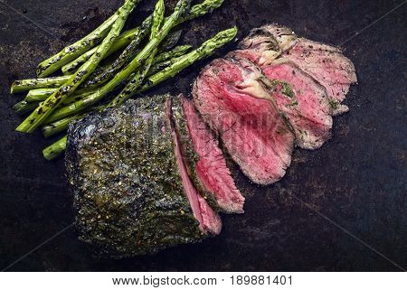Barbecue Wagyu Roast Beef with green Asparagus as close-up on old metal sheet