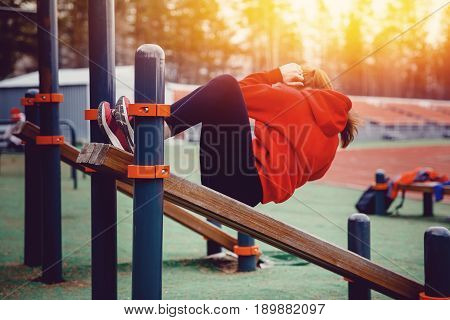 The girl on the sports ground pumps the press on the bench. The concept of a healthy lifestyle and exercises to strengthen the back.