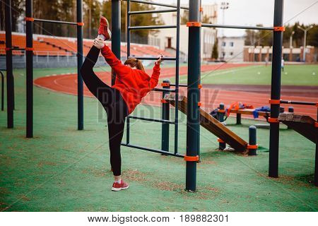 Girl on the sports field stretches the muscles of the legs and back, vertical twine. Concept of a healthy lifestyle and exercises to strengthen the hands and back and joints.