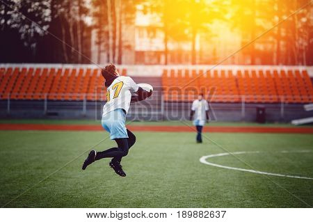 Guy with the team is throwing throwing and catching with flying disk at the sports stadium. Concept of the game is active and mobile in summer. Sunny highlight.