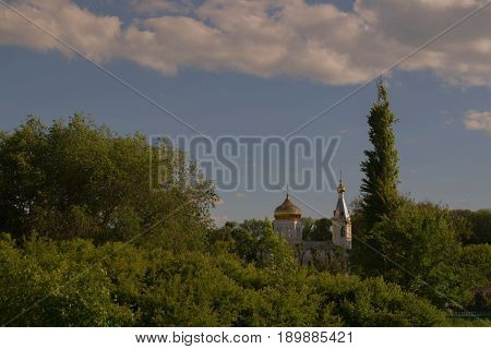 Gilded monastery domes among green trees against a blue sky with white clouds