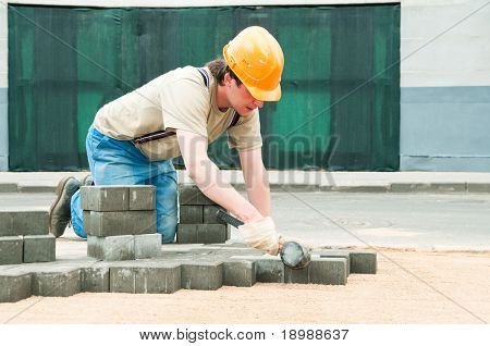 mason worker making sidewalk pavement with stone blocks
