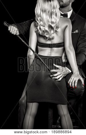 Man in tux with whip grab woman lover ass by hand black and white selective coloring isolated